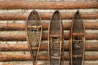 Snow shoes hanging on a log cabin