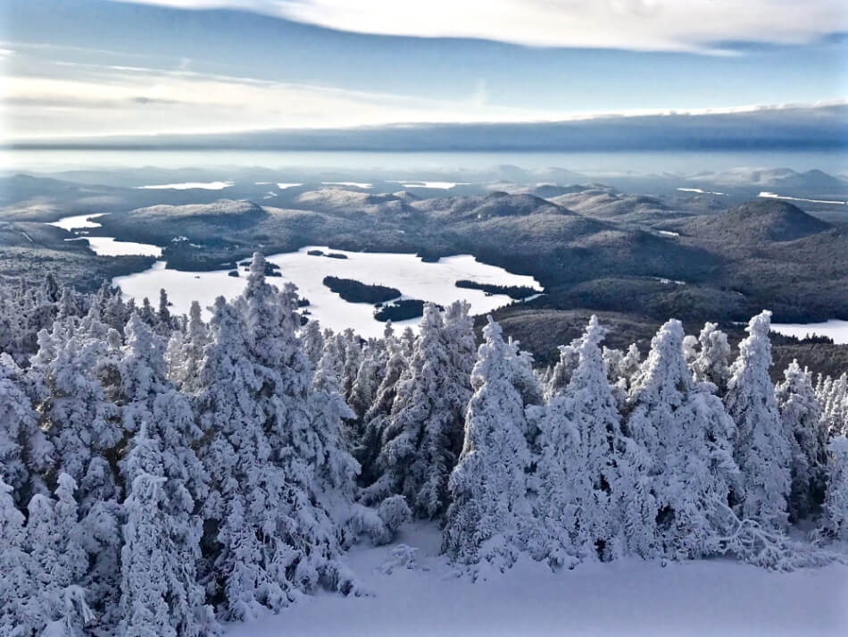 mountain top view showing snow covered trees and several lakes