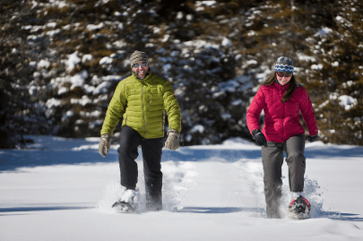 Two individuals snowshoeing in deep snow