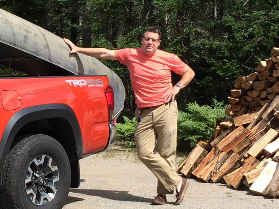 Jason Barden standing next to red pickup truck with canoe on back